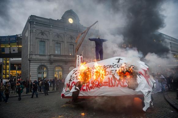 ब्रसेल्स में यूरोपीय संसद के बाहर घास-फूस जलाकर प्रदर्शन करते दुग्ध उत्पादक किसान।