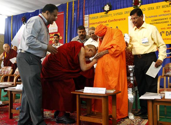 बांग्लादेश के उत्तर पश्चिम में स्थित तुमकुर विवि परिसर में 'विश्व शांति में मानव की भूमिका' विषय पर आयोजित संगोष्ठी में पहुंचे 105 साल के हिंदू धर्मगुरु शिवकुमारा स्वामी का झुककर अभिवादन करते तिब्बती धर्मगुरु दलाई लामा।