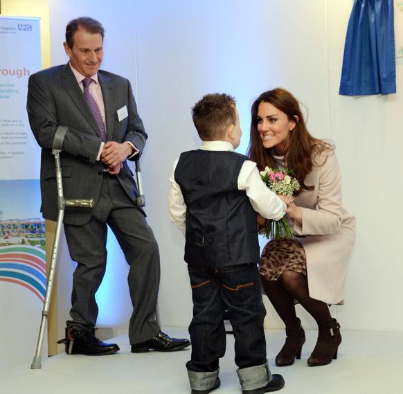 इंग्लैंड के पीटरबर्ग स्थित एक अस्पताल में डचेज ऑफ कैंब्रिज को फुलों का बुके देकर स्वागत करता एक सात वर्षीय बालक जेमी एंड्रू।