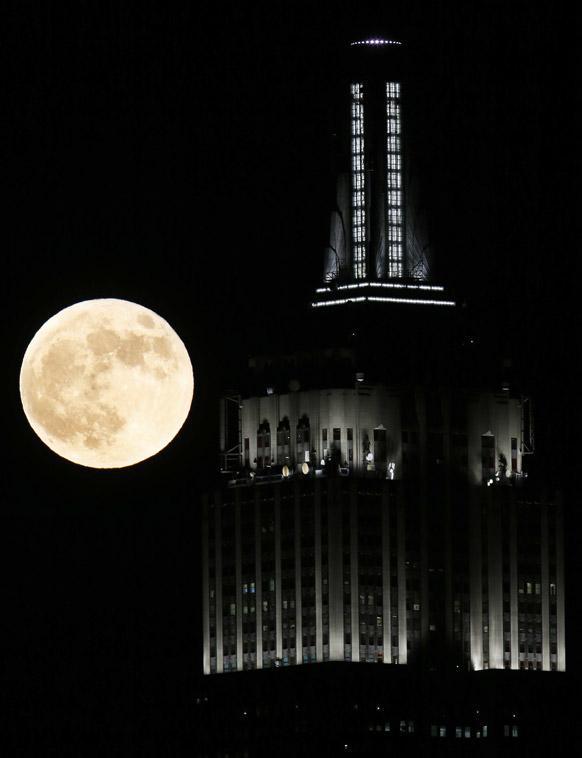 न्यूजर्सी के होबोकन स्थित एम्पायर स्टेट बिल्डिंग के बगल से पूर्ण चंद्रमा का नजारा।