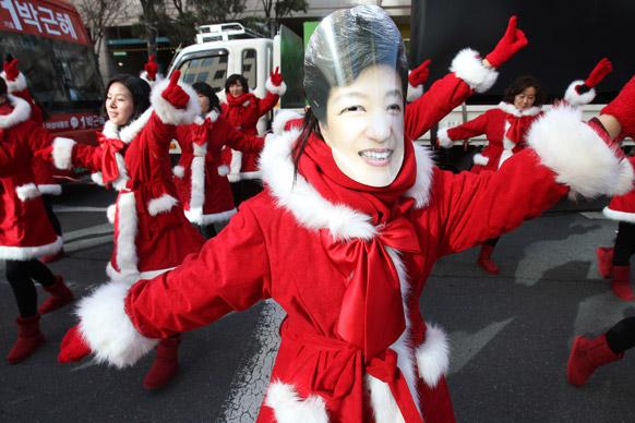 दक्षिण कोरिया के सियोल में राष्ट्रपति चुनाव प्रचार अभियान के दौरान पार्क गुअेन ही का मास्क पहने हुए उनके समर्थक।