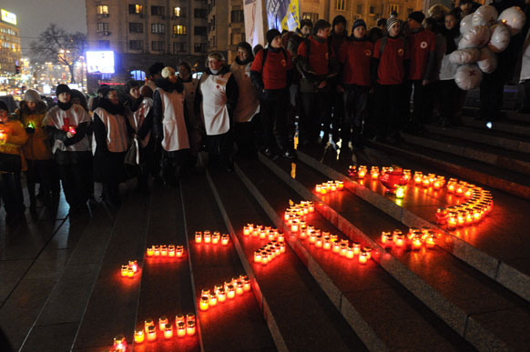 यूक्रेन के किव में विश्व एड्स दिवस पर रेड रिबन की आकृति को मोमबत्ती से सजाते यूक्रेन के लोग।