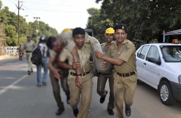 ओडिशा की राजधानी भुवनेश्वर में विधानसभा भवन के समीप नौकरी की सुरक्षा और वेतन बढ़ाने की मांग को लेकर शिक्षकों के प्रदर्शन के दौरान हुई हिंसक झड़प के बाद घायल पुलिसकर्मी को इलाज के लिए ले जाते साथी पुलिसकर्मी।