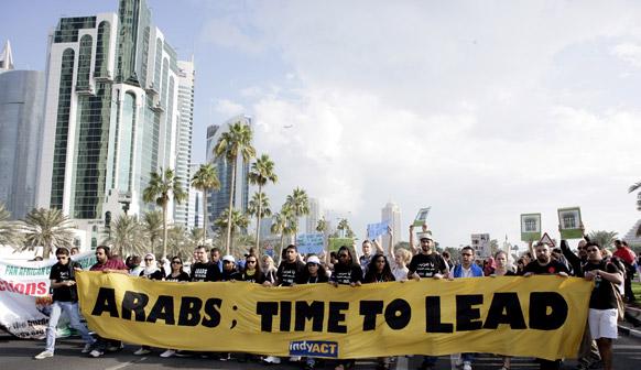 दोहा में जलवायु परिवर्तन पर ठोस कार्रवाई की मांग को लेकर रैली निकालते अंतरराष्ट्रीय एवं स्थानीय कार्यकर्ता।