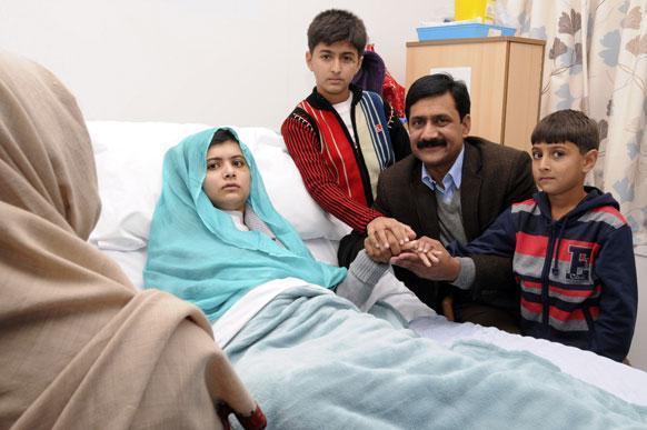 इंग्लैंड के बर्मिंघम में स्थित क्वीम एलिजाबेथ अस्पताल से जारी तस्वीर में अस्पताल के बेड पर मलाला यूसुफजई और साथ में मलाला के पिता जियाउद्दीन व दो छोटे भाई अटल और खुशहाल।