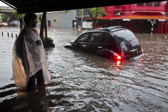 अर्जेंटीना की राजधानी ब्यूनस आयर्स में आई बाढ़ की वजह से सड़कों पर भारी जलजमाव में फंसी कार और नजारे से सहमा समीप के स्टैंड पर खड़ा एक शख्स।