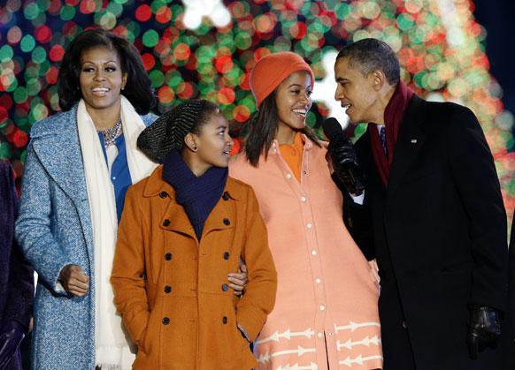 व्हाइट हाउस में आयोजित 90वीं सालाना राष्ट्रीय क्रिसमस ट्री लाइटिंग समारोह के दौरान क्रिसमस के धुन पर अपनी बेटियों साशा ओबामा और मालिया ओबामा के साथ गुनगुनाते अमेरिकी राष्ट्रपति बराक ओबामा, अमेरिकी की प्रथम महिला मिशेल ओबाम।