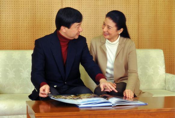 टोक्यो में अपने आवास में फोटो बुक को निहारते जापान के क्राउन युवराज नारुहितो (बाएं) और क्राउन राजकुमारी मासाको।