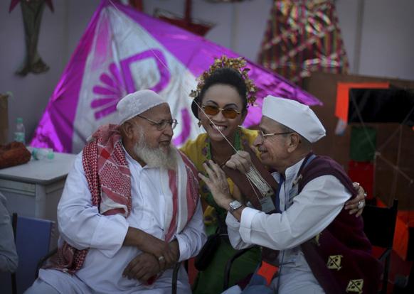 नई दिल्ली में दो बुजुर्ग प्रतिभागी के साथ पतंग महोत्सव में भाग लेने आई इंडोनेशिया की प्रतिभागी (बीच में)।