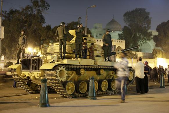 मिस्र की राजधानी काहिरा में राष्ट्रपति भवन के बाहर सुरक्षा में लगाए गए सेना टैंक पर बैठे बच्चे की मोबाइल से तस्वीर लेते प्रदर्शनकारी।