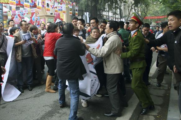 वियतनाम की राजधानी हनोई में प्रदर्शनकारियों की रैली को रोकने का प्रयास करती वियतनाम की पुलिस।
