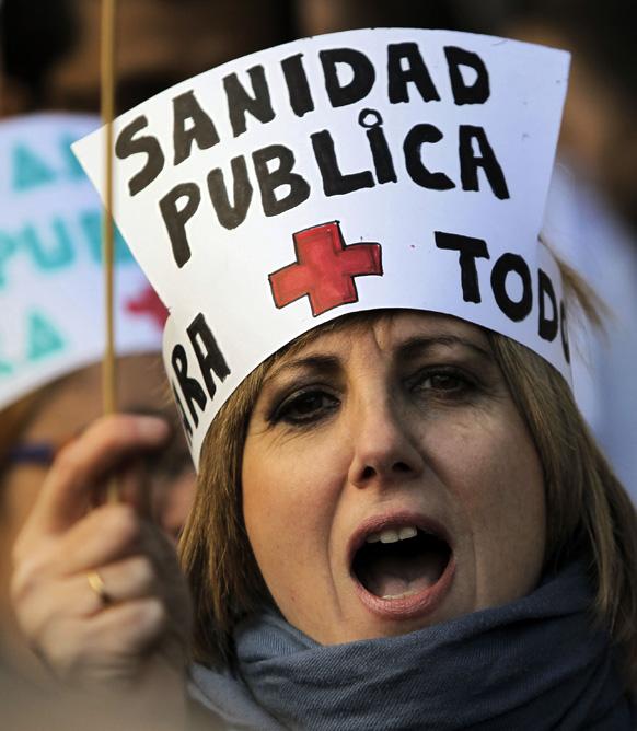 स्पेन के मैड्रिट में पब्लिक हेल्थ केयर सिस्टम के सुधार के लिए प्रदर्शन करते लोग।