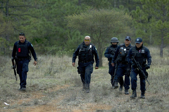 मेक्सिको में सिंगर जेन्नी रिवेरा के प्लेन क्रैश स्थल की ओर जाते हुए पुलिसकर्मी।