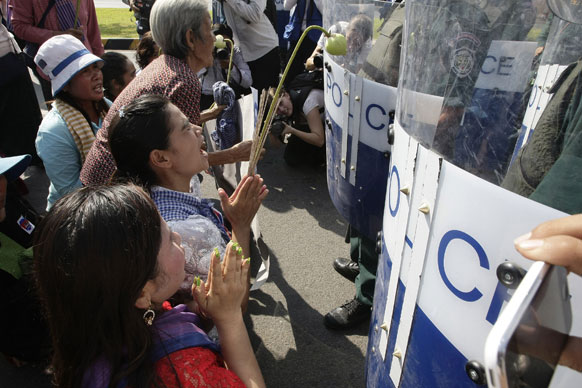 कंबोडिया से नामपेन्ह में अपनी जमीन के टाइटल्स की मांग को लेकर मिनिस्टर ऑफ काउंसिल को आवेदन देने के लिए पुलिस के सामने निवेदन करते प्रदर्शनकारी।