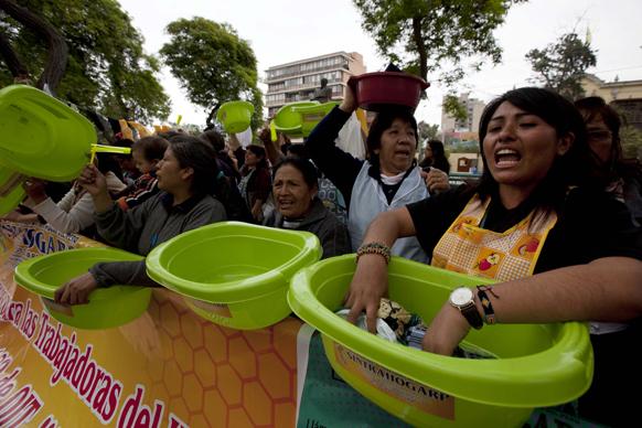 पेरू में श्रम मंत्रालय के सामने घर में काम करने वाली महिलाएं वॉशबॉवेल के साथ प्रदर्शन करती हुईं।