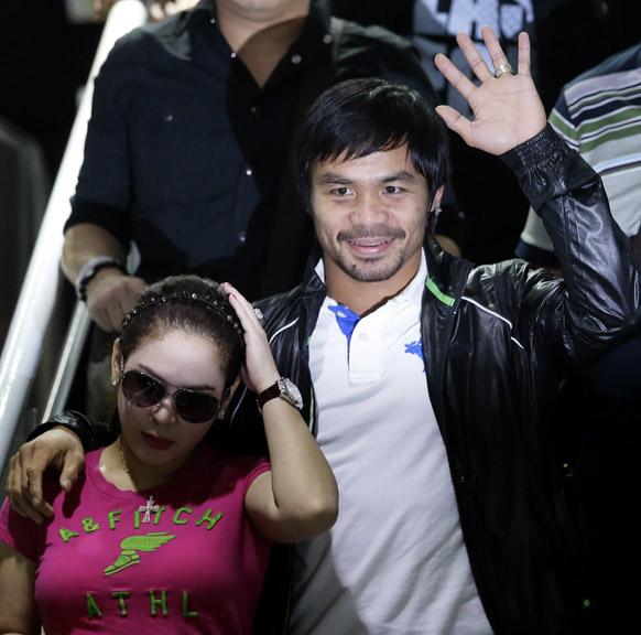 मनीला में फिलीपीन्स के बॉक्सर मन्नी पक्वीओ अपनी पत्नी के साथ हाथ हिलाकर लोगों का अभिवादन स्वीकार करते हुए।