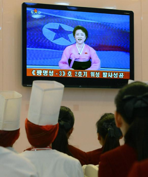 उत्तर कोरिया के प्योंगयांग में टीवी देखेते रेस्टोरेंट के कर्मचारी।