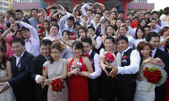 मलेशिया के कुआलालांपुर में सामूहिक विवाह समारोह में फोटो सेशन के दौरान कपल्स।