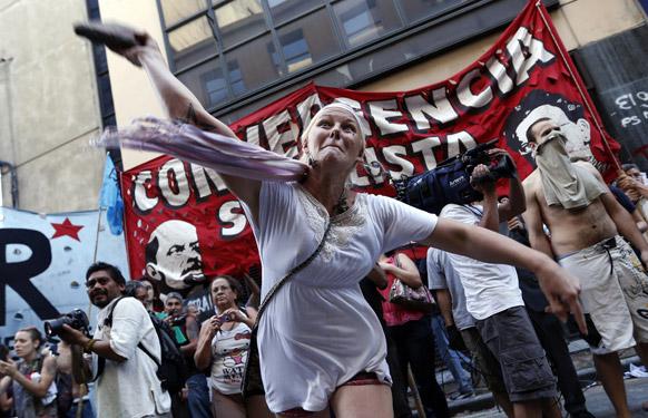 अर्जेंटीना में एक गायब युवा महिला के समर्थन में विरोध प्रदर्शन के दौरान पुलिस पर पत्थर फेंकते हुए प्रदर्शनकारी।