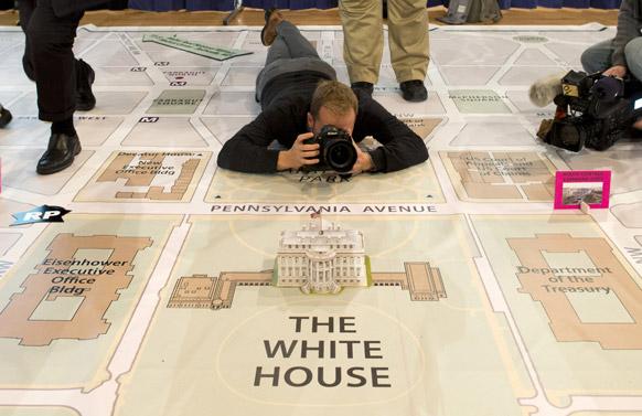 अमेरिका में एक न्यूज फोटोग्राफर व्हाइट हाऊस के मॉडल की तस्वीर अपने कैमरे में कैद करता हुआ।