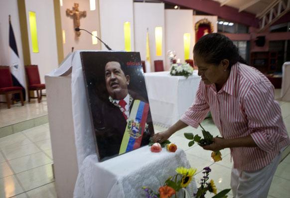 निकारागुआ में वेनेजुएला के राष्ट्रपति हूगो शावेज की तस्वीर के सामने फूल अर्पित करती हुई एक महिला।