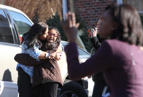 गोलीबारी की घटना के बाद स्कूल के बाहर अपनी पुत्री को चूमती एक महिला।