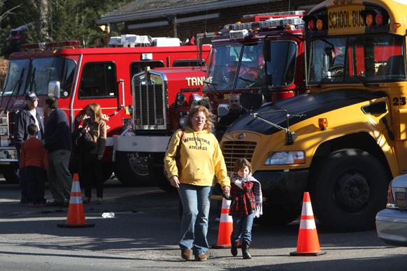गोलीबारी की घटना के बाद अपने बच्चों को स्कूल से दूर ले जाते परिजन।