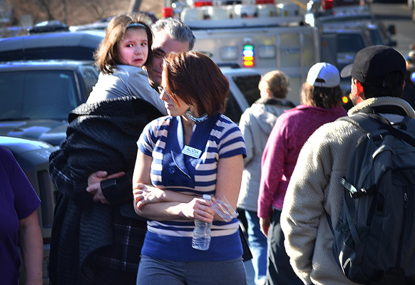 गोलीबारी की घटना के बाद एक महिला अपने परिवार के साथ।