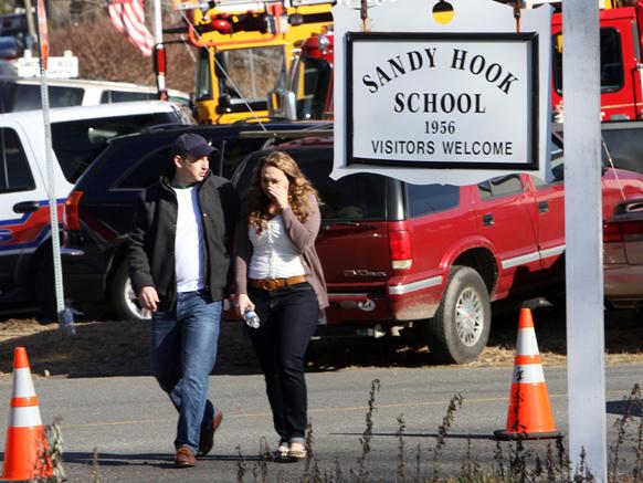 स्कूल में गोलीबारी की घटना के बाद स्कूल से दूर जाते अभिभावक।