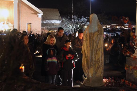 लीमा चर्च के बाहर मैरी की प्रतिमा के समक्ष प्रार्थना करते परिवार।