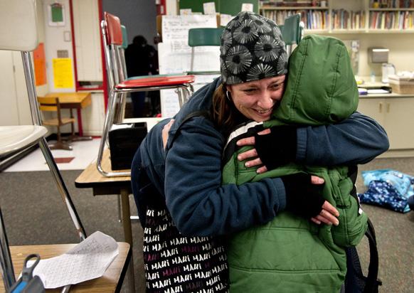 कनेक्टिकट के स्कूल में गोलीबारी की घटना न्यूज चैनल पर सुनने के बाद स्कूल के समीप अपने बच्चे को सीने से लगाती एक महिला।