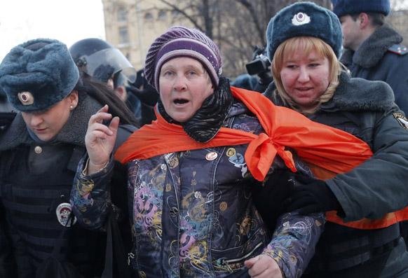 मास्को में बिना अनुमति के रैली निकालने पर एक प्रदर्शनकारी को काबू में करती पुलिस।