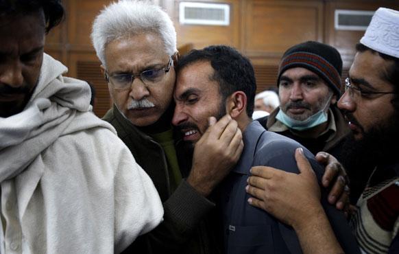 पेशावर में एक अस्पताल में हुए धमाके के बाद एक पीड़ित परिजन को सांत्वना देते लोग।