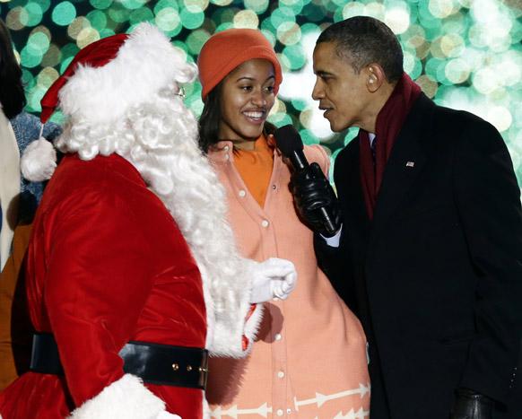 वाशिंगटन: व्हाइट हाऊस में नेशनल ट्री लाइटिंग सेरेमनी के दौरान सांता क्लाज के पहुंचने के बाद गुनगुनाते हुए अमेरिका के राष्ट्रपति बराक ओबामा और उनकी बेटी मालिया ओबामा।
