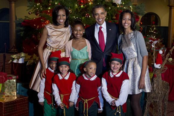 वाशिंगटन में नेशनल बिल्डिंग म्यूजयिम में एल्वस की वेश-भूषा में बच्चों के साथ पोज देते हुए अमेरिका के राष्ट्रपति बराक ओबामा, मिसेल ओबामा, मालिया एंड साशिया ओबामा।
