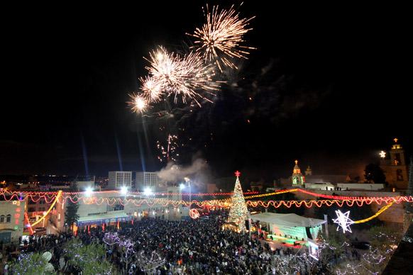 बेथलेहम में मेंगर स्वायर के निकट क्रिसमस ट्री लाइटिंग का आनंद लेते हुए फिलीस्तीन के निवासी।