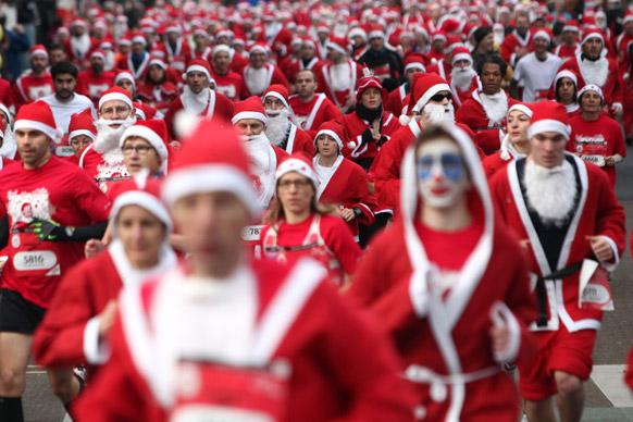 पेरिस के इस्सी लेस मोलीनियोक्स की गलियों में पारंपरिक क्रिसमस कोरिडा रेस में सांता क्लाज की ड्रेस पहनकर भाग लेते प्रतिभागी।
