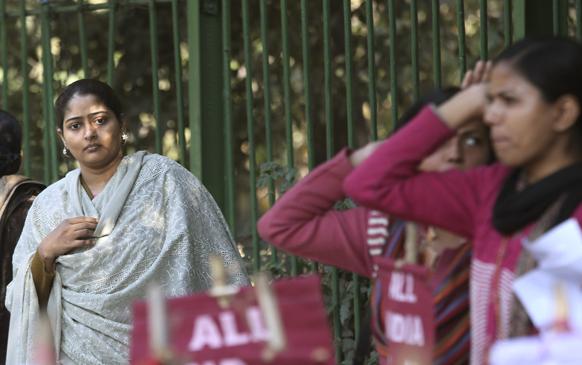 नई दिल्ली में गैंग रेप के विरोध में प्रदर्शन करते प्रदर्शनकारियों को देखती एक महिला।