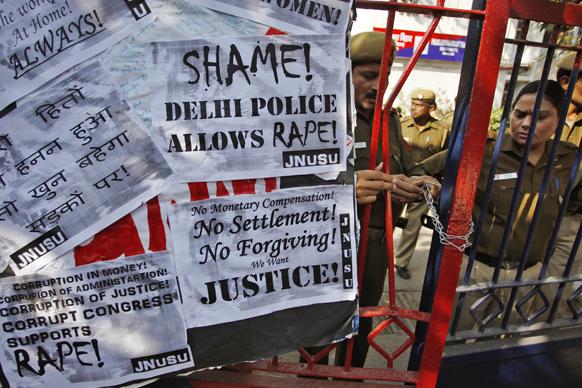 नई दिल्ली में गैंग रेप के विरोध में प्रदर्शन के दौरान पुलिसकर्मी थाने का गेट बंद करते हुए।