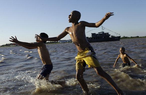 लैटिन अमेरिका में समुद्री लहरों से खेलते युवक।
