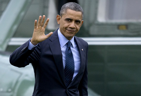 वाशिंगटन में व्हाइट हाउस के मरीन वन से ओवल कार्यालय के लिए जाते अमेरिकी राष्ट्रपति बराक ओबामा हाथ हिलाकर मीडिया का अभिवादन कर रहे हैं।