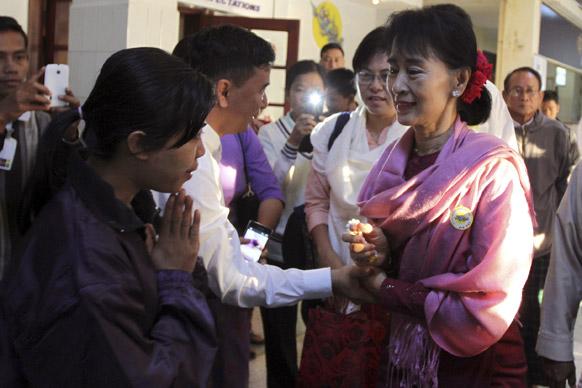 यंगून हवाईअड्डे पर म्यांमा की विपक्षी नेता आंग सान सू ची का स्वागत करते उनके समर्थक।