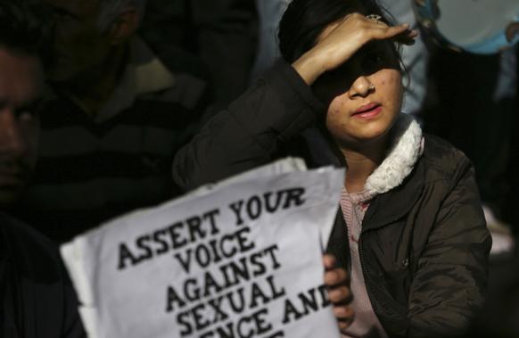 नई दिल्ली में गैंग रेप के विरोध में मुख्यमंत्री शीला दीक्षित के घर के बाहर तख्तियों के साथ प्रदर्शन करती युवती।