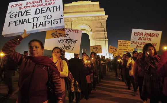 नई दिल्ली के इंडिया गेट पर गैंग रेप के विरोध में तख्तियों पर नारे लिखकर कैंडिल मार्च करते लोग।