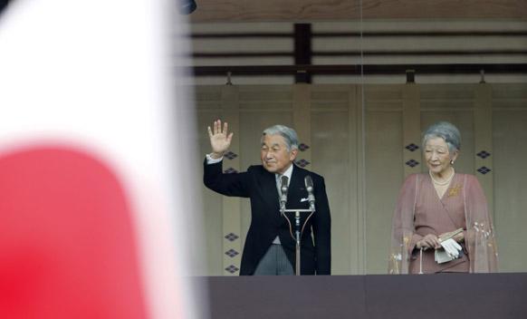 टोक्यो में हाथ उठाकर अपने शुभचिंतकों का अभिवादन स्वीकार करते जापान के राजा अकिहितो। साथ में हैं महारानी मिशिको।