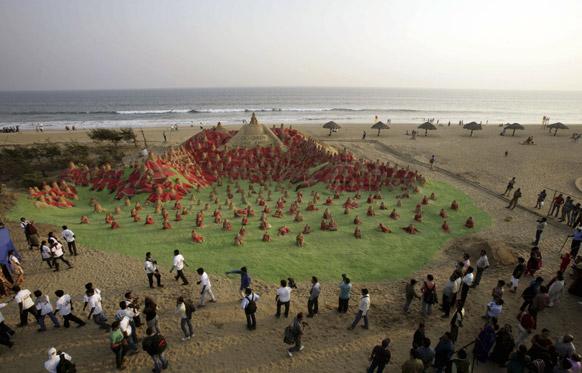 पुरी में क्रिसमस त्योहार से पहले रेत से बनाए गए सैंटा क्लॉज को देखते लोग।