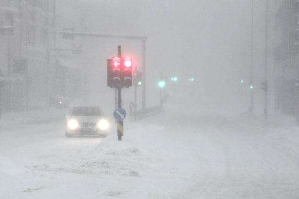नार्वे में बर्फीले तूफान के बीच एक कार।