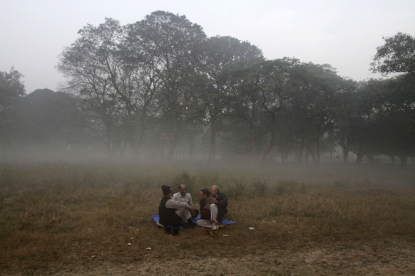 कोलकाता में सुबह के वक्त एक खेत में बैठे लोग।