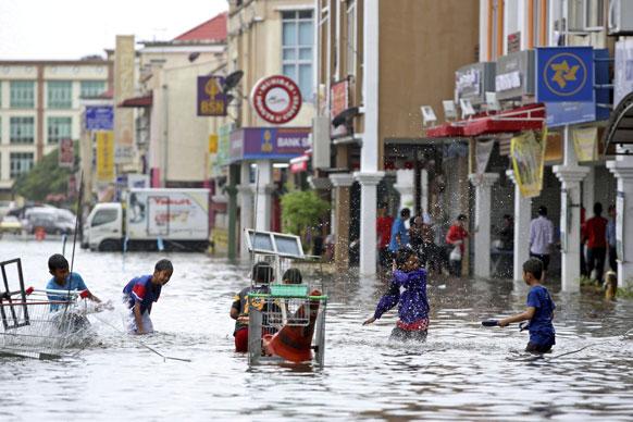 मलेशिया में भारी बारिस के बाद शहर के नीचले हिस्से में आई बाढ़ के पानी में खेलते बच्चे।
