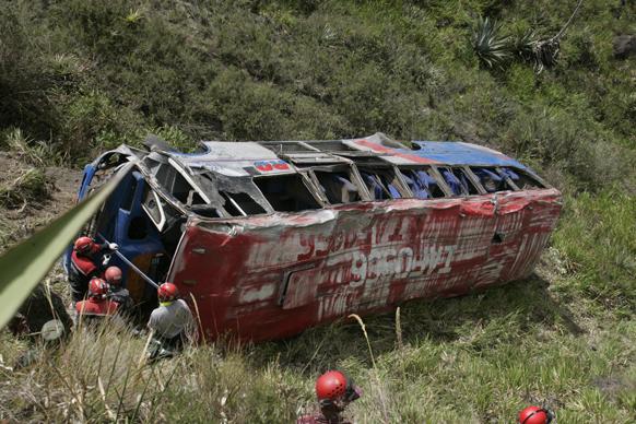 इक्वाडोर में एक दुर्घटनाग्रस्त बस से घायलों को बाहर निकालते हुए पुलिस अधिकारी और बचावकर्मी।
